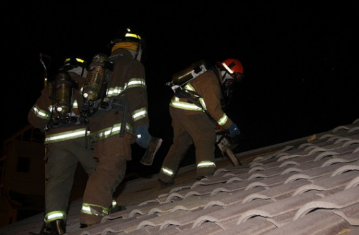 Firefighter begins chainsawing into an adobe roof